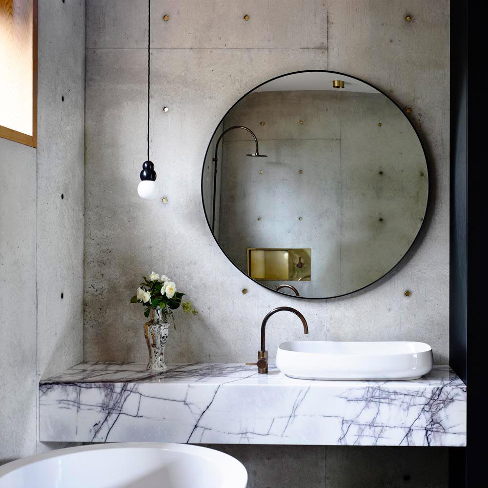 Badezimmer mit feiner weißer Marmorplatte mit Messinghähnen.